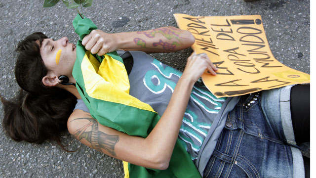 """PHOTO:A protester lies on the ground in front of a police line in Rio de Janeiro, Brazil, Sunday, June 16, 2013. Her sign reads """"To hell with the World Cup."""" Plans to increase bus fares sparked a wave of protests in Brazil last week."""