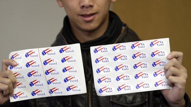 PHOTO:Student clerk Tua Her offers stickers to voters at a fire station in Stockton, Calif. Young voters who are less likely to be engaged in other election cycles are being credited with making the difference this year in California