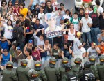 PHOTO:Opposition supporters and students, some holding pictures of opposition presidential candidate Henrique Capriles, confront riot police as they block a highway in the Altamira neighborhood of Caracas, Venezuela, Monday, April 15, 2013.