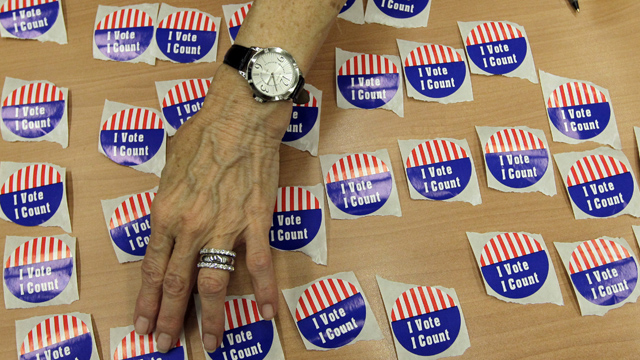 """PHOTO:An election judge arranges """"I Vote, I Count"""" stickers on a table in the Marion County Clerks office as voterscast early ballots in Indianapolis, Monday, Oct. 22, 2012."""