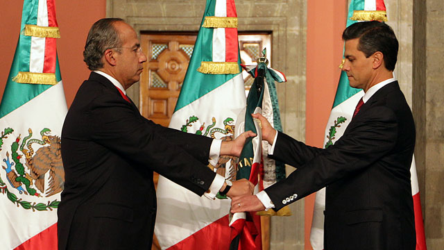 PHOTO: Mexicos outgoing president, Felipe Calderon, left, gives a Mexican flag to president-elect Enrique Pena Nieto during the official transfer of command ceremony at the National Palace in Mexico City, Saturday Dec. 1, 2012.