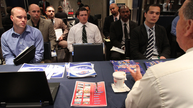 Veterans listen as a representative from White Rose Foods, foreground right, talks about their agency during a job fair introducing veterans to careers in the security and private investigations industry at Yankee Stadium in the Bronx borough of New York.