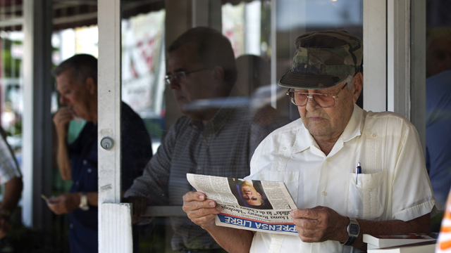 PHOTO:Nino Diaz reads a Spanish language newspaper at a Cuban cafe in Miamis Little Havana section.