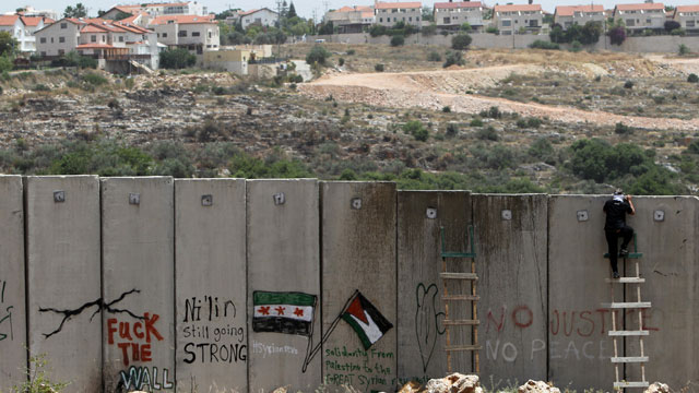 PHOTO:A palestinian protester climbs Israel's controversial West Bank barrier.