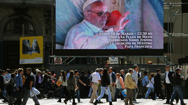 PHOTO: A screen in Buenos Aires, Argentina invites people to gather in the Plaza de Mayo to watch the Popes inauguration ceremony. Catholics around the world expect different things from the new Pope.