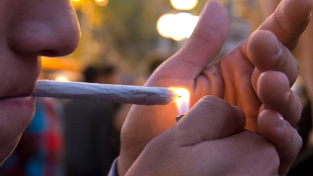 PHOTO:A young man lights a marijuana cigarette during a demonstration demanding a new law on cannabis in Montevideo on May 8, 2013.