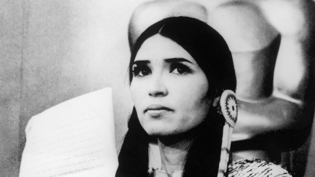PHOTO: 27th March 1973: Sacheen Littlefeather (actor Maria Cruz in Native American makeup) holds a written statement from actor Marlon Brando refusing his Best Actor Oscar on stage at the Academy Awards, Los Angeles, California.