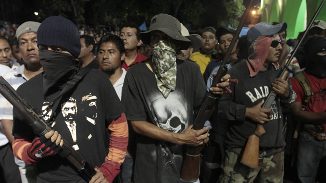 PHOTO:Hooded men stand guard while passing detainees to the Government of the State of Guerrero by the communitarian police at the central square of Ayutla de los Libres, on Febrary 8, 2013. On Tuesday, a final batch of 39 detainees was released.