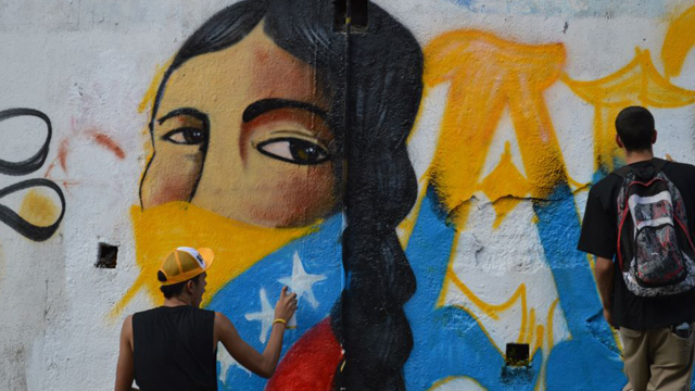 PHOTO: Jesus Garcia from the Chavista youth collective Antimantuanos paints a patriotic mural in Caracas. Young Chavez supporters say they will support the revolution no matter who is at the helm.
