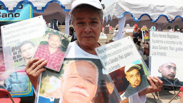 PHOTO: Maria Herrera holds the portraits of four of her children who have gone missing since 2008 and a portrait of a human rights activist killed in 2011.