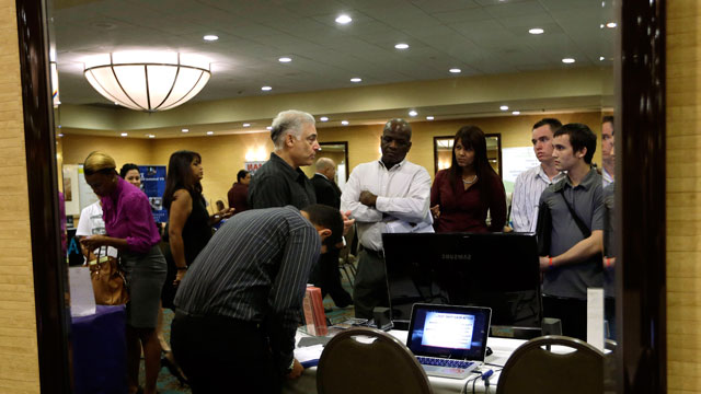 PHOTO:Robert Orkin, of the company TxT-Alert, third from left, talks with job seekers during a job fair held by National Career Fairs, in Fort Lauderdale, Fla.