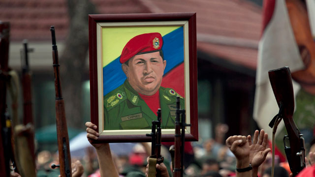 PHOTO: Members of the National Revolutionary Militia, also called Bolivarian militias, hold up their guns and a painting of Venezuelas President Hugo Chavez.