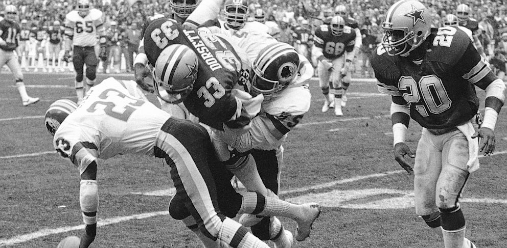 PHOTO: Dallas Cowboys running back and Hall of Famer Tony Dorsett (33) takes a hard hit against the Washington Redskins in Washington. Dorsett was one of 4,500 former players who settled a concussion-related lawsuit with the NFL for $765 million.