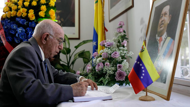 PHOTO: Cubas Vice President of the Council of State, Jose Ramon Machado Ventura, writes in a book of condolence for Venezuelas late President Hugo Chavez