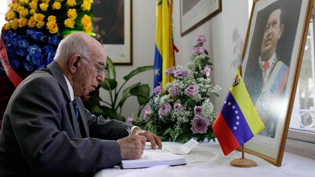PHOTO:Cubas Vice President of the Council of State, Jose Ramon Machado Ventura, writes in a book of condolence for Venezuelas late President Hugo Chavez