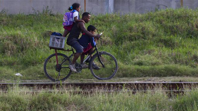 PHOTO: A man and two students ride a bicycle after leaving school in Havana, Cuba, Tuesday Nov. 20, 2012.