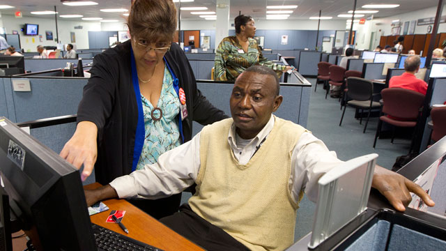 PHOTO:WorkForce One staffer Rose Capote-Marcus works with a client, Pen Osuji as he works on job applications.