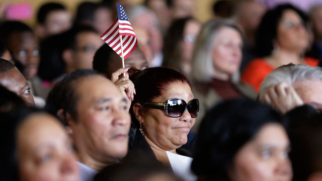 PHOTO: Paula Henriquez, of Boston, originally of The Dominican Republic, center, waves an American flag during aNaturalization Oath Ceremony at the John F. Kennedy Presidential Library and Museum, in Boston, Wednesday, March 6, 2013.