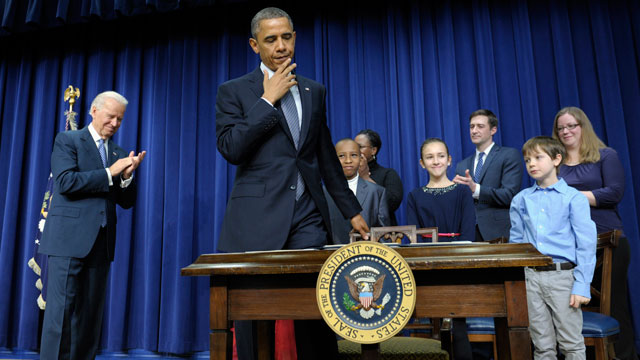 PHOTO: President Barack Obama, accompanied by Vice President Joe Biden and children who wrote the president about gun violence following last months shooting at an elementary school in Newtown, Conn., prepares to sit down to sign executive orders.