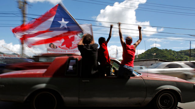 People ride atop a vehicle waving a Puerto Rican flag during elections in San Juan, Puerto Rico, Tuesday, Nov. 6, 2012. Puerto Ricans are electing a governor as the U.S. island territory does not get a vote in the U.S. presidential election.