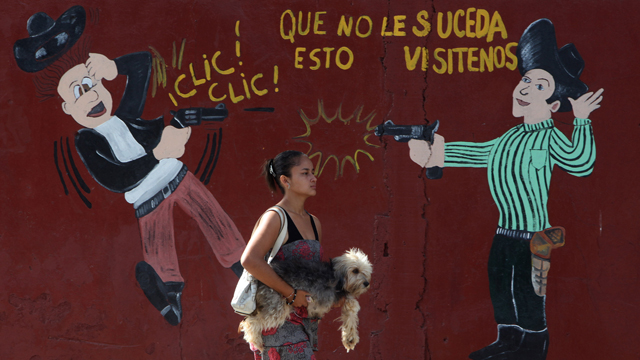 PHOTO:A woman carries her dog past an armory shop in San Pedro Sula, Honduras. Honduras has more homicides than any other country in the world with 91 per 100,000 people, the World Health Organization says.