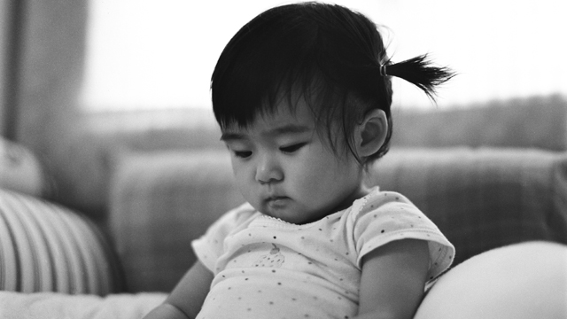 PHOTO:Baby with braids sitting on bed looking down