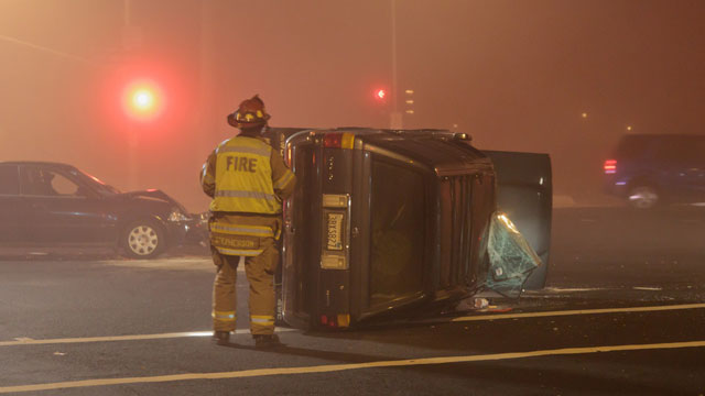 PHOTO:A Roseville Fire Department firefighter looks over an overturned vehicle after a collision at Blue Oaks Boulevard and Woodcreek Oaks Boulevard in Roseville, California on 11/26/2011