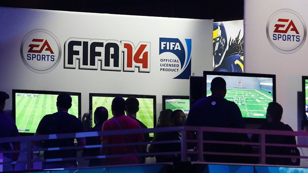 Attendees try out Electronic Arts Inc.'s FIFA 14 and Madden NFL 25 video games at the company's booth during the E3 Electronic Entertainment Expo in Los Angeles, California, U.S., on Wednesday, June 12, 2013. E3, a trade show for computer and video games, draws professionals to experience the future of interactive entertainment as well as to see new technologies and never-before-seen products.