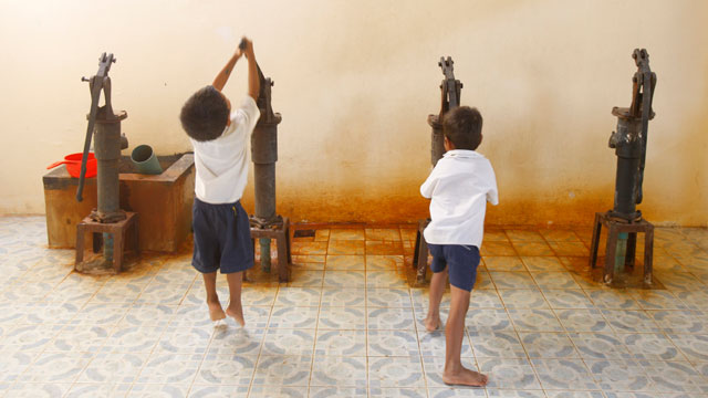 PHOTO:Children pump water at a school in Cambodia in 2010.