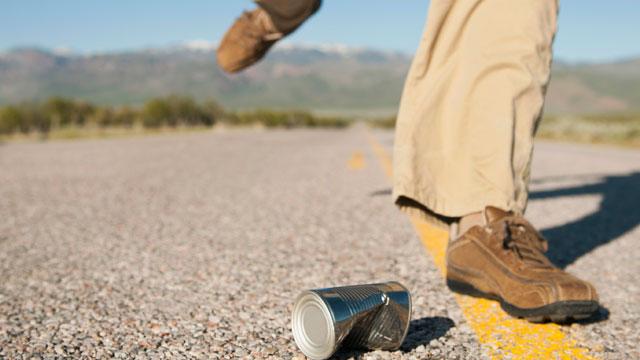 PHOTO:USA, Utah, Kanosh, Man kicking tin can on otherwise empty road.