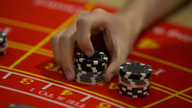 PHOTO:A student handles gaming chips during a demonstration at a blackjack table at the Macao Polytechnic Institute (MPI) Gaming Teaching and Research Centre in Macau, China, on Tuesday, June 18, 2013.