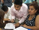 PHOTO:Bolivian Diego Mariaca(C), his mother Ingrid Vaca(R) and brother Gustavo Mariaca(L) fill out deferred action paperwork, August 15, 2012 at the National Immigration Forum in Washington, DC.