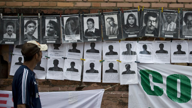 PHOTO:A man looks at portraits of victims during the State-Sponsored Crime Victims International Day in Cali, Colombia.