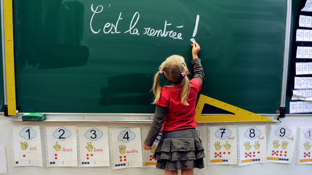 PHOTO:A little girl writes on the blackboard 'C'est la rentrée' (Its the Start of the school year) at the school Jules Ferry in Bethune, northern, France, on August 28, 2012.