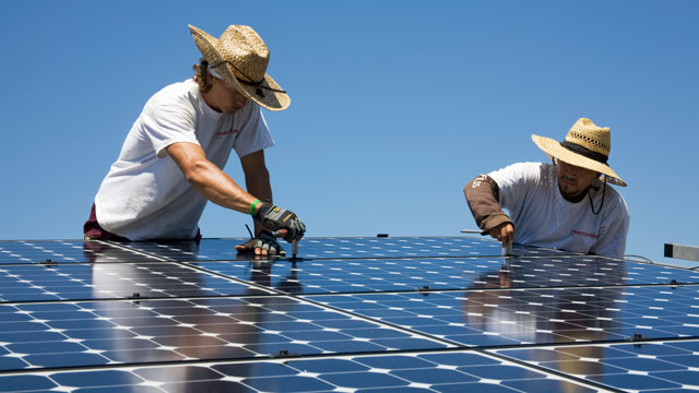 PHOTO: Green workers install a residential grid-tied solar array on a hillside in Malibu, California, USA.