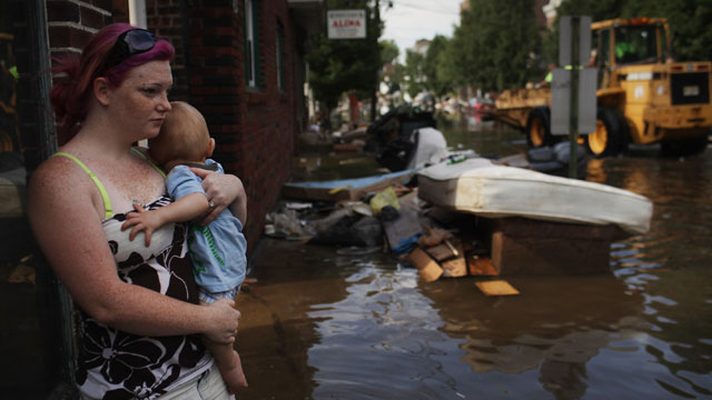 PHOTO:A woman and her baby look out over a flooded street on August 31, 2011 in Wallington, New Jersey. New Jersey was especially hard hit by Hurricane Irene with thousands of residents forced into shelters due to flooded homes.