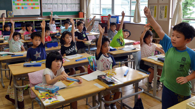 PHOTO:Six-year-old Japanese elemetary student Seishi Nishida (2nd row L blue shirt) raises his hand along with classmates at school in Tokyo on June 11, 2013.