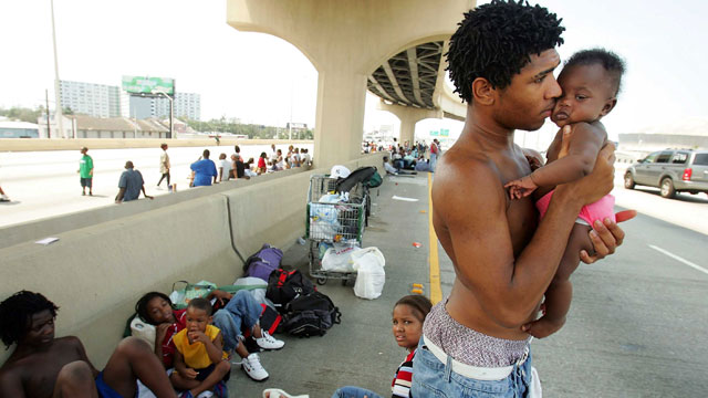 PHOTO:Daryl Thompson holds his 3-month old daughter Dejanae as they wait with other displaced residents on a highway in the hopes of catching a ride out of town August 31, 2005 in New Orleans.