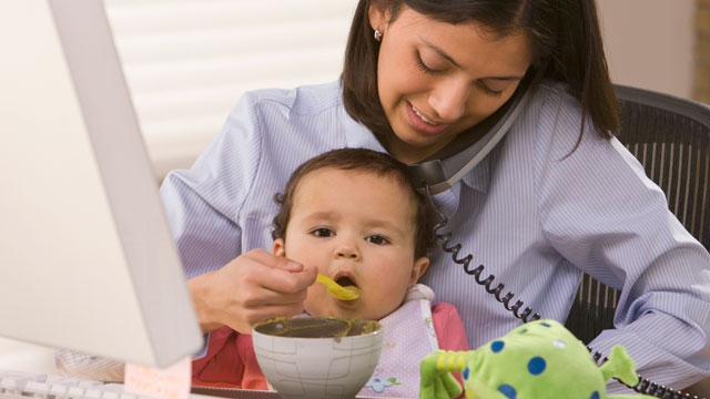 PHOTO: A woman feeds her daughter and works.