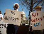 PHOTO: Tabu Henry Taylor (C) of Washington D.C., and Mike Crowe (R) of Springfield, Virginia, join a handful of protesters from anti-amnesty groups to demonstrate in front of the U.S. Capitol building on April 10, 2013.