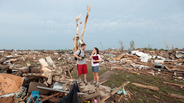 PHOTO: Carlos and Kim Caudillo stand in the debris of their home after a tornado ripped through Moore, Oklahoma on May 20, 2013. The tornado, reported to be at least EF4 strength and two miles wide, touched down on Monday killing at least 51 people.