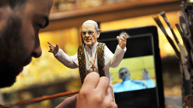 PHOTO:Artisan Genny Di Virgilio paints a hand-crafted figurine of Pope Francis.