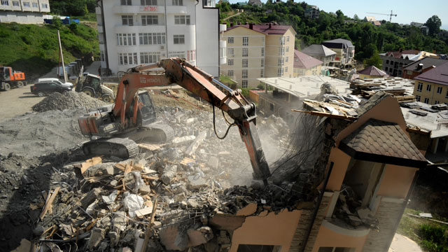PHOTO: An excavator demolishes a building in the Russian Black Sea resort of Sochi on May 15, 2013 . The three-storey apartment building began leaning after a tunnel being constructed for the 2014 Winter Olympics collapsed nearby, the local media said.