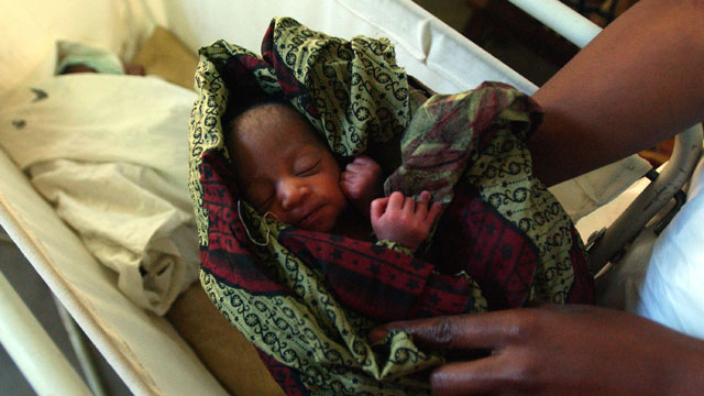 PHOTO: An orphan child of a Malawian woman who died while giving birth to triplets is cared for at the community child care program at Michinji District Hospital June 29, 2002 in Michinji, Malawi.