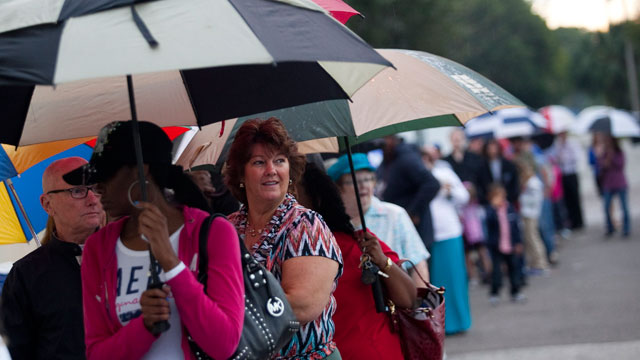 PHOTO: Lines of voters wait in the rain to cast their ballots as the polls open November 6, 2012 in St. Petersburg, Florida.