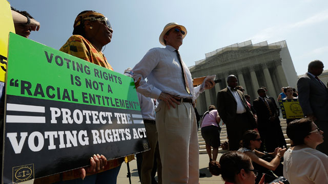 PHOTO: Supporters of the Voting Rights Act listen to speakers discussing rulings outside the U.S. Supreme Court building on June 25, 2013 in Washington, DC.