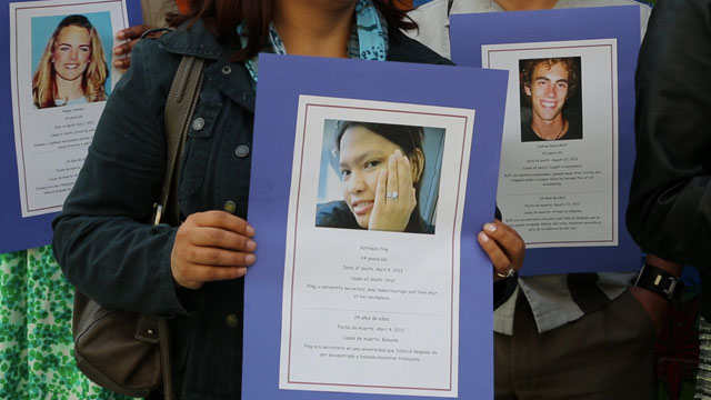 PHOTO: Demonstrators hold photographs of individuals who died at work.