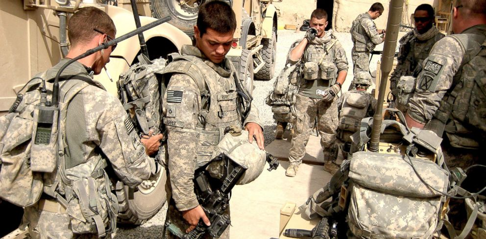 PHOTO: 10th Mountain Division cavalry scouts prepare to patrol in Kandahar, Afghanistan, in 2010 by checking gear including electronic jammers to defeat radio-detonated hidden bombs.