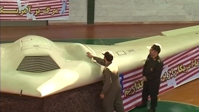 PHOTO: A military official gives a tour of an intact RQ-170 drone in a hangar to another Iranian military official.