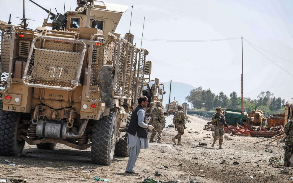 Members of the Afghan security forces inspect the site of a suicide bomb attack targeting a convoy of U.S. forces near Nangarhar airport, which is used as a U.S. military base, in Jalalabad, the capital of eastern Nangarhar province, Afghanistan, April 10, 2015.